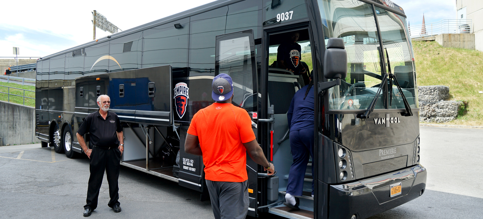 Sports team getting on Premiere bus with driver